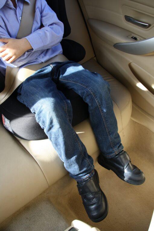 jambes d'enfant assis dans son siège auto avec ses jambes qui pendent dans le vide